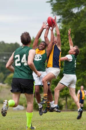 Roswell, GA, EE.UU. - 17 de mayo 2014: Los jugadores saltan y compiten por la pelota en un juego de aficionados de fútbol australiano en un parque de la ciudad de Roswell. Foto de archivo - 30552073