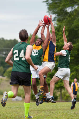 Roswell, GA, Verenigde Staten - 17 mei 2014: Spelers springen en te strijden om de bal in een amateur spel van Australisch voetbal in een Roswell stadspark.