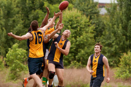 Roswell, GA, USA - May 17, 2014:  Several players jump to catch ball in an amateur club game of Australian Rules Football in a Roswell city park. 新聞圖片