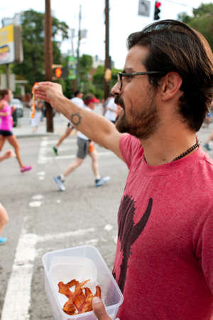 Atlanta, GA, USA - July 4, 2014:  An unidentified man gives out strips of bacon to exhausted runners as they near the finish line of the Peachtree Road Race.