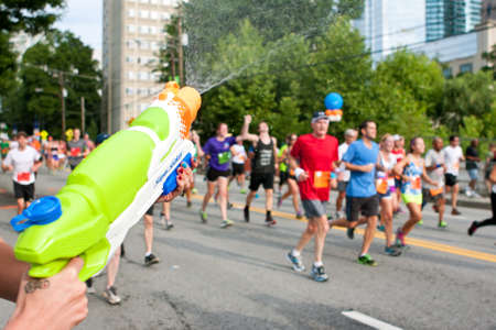 soaks: Atlanta, GA, USA - July 4, 2014:  A woman soaks runners with a squirt gun as they head toward the finish line of the Peachtree Road Race. Editorial