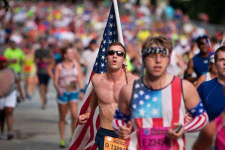 Atlanta, GA, USA - 4. Juli 2014: Ein junger Mann trägt einen großen amerikanischen Flagge auf seine Schulter, als er unter Tausenden von anderen Menschen kurz vor der Ziellinie der Peachtree Road Race läuft. Standard-Bild - 31550390