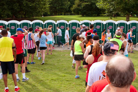 Atlanta, GA, USA - July 4, 2014:  Exhausted runners wait in long lines to use a Johnny On The Spot portable toilet, after just completing the Peachtree Road Race 10K.