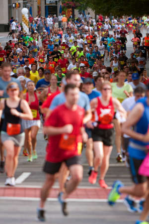 adrenaline rush: Atlanta, GA, USA - July 4, 2014:  Thousands of runners make their way down Peachtree Street on their way to the finish line of the Peachtree Road Race