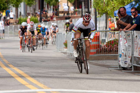 adrenaline rush: Duluth, GA, USA - August 2, 2014:  A male cyclist separates himself from a group of racers competing in the Georgia Cup Criterium event.