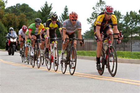 bunched: Duluth, GA, USA - August 2, 2014:  Cyclists bunched together in a pack race through a straightaway in the Georgia Cup, a criterium event held on the streets of downtown Duluth. Editorial