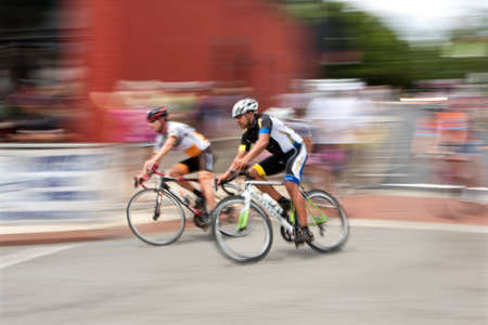 adrenaline rush: Duluth, GA, USA - August 2, 2014:  Colorful motion blur of two cyclists speeding by as they compete while racing in the Georgia Cup, a criterium event held on the streets of downtown Duluth.