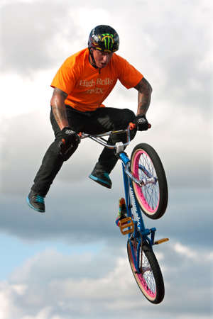 exhilerating: Hampton, GA, USA - September 27, 2014:  A young man with the High Roller BMX club rotates his bike in midair while performing a BMX stunt at the Georgia State Fair. Editorial