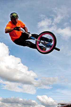 Hampton, GA, USA - September 27, 2014:  A young man with the High Roller BMX club rotates his bike in midair while performing a BMX stunt at the Georgia State Fair. Editorial