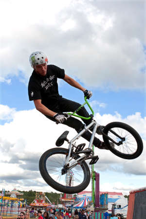 exhilerating: Hampton, GA, USA - September 27, 2014:  A young man with the High Roller BMX club spins his bike in midair while performing a BMX stunt at the Georgia State Fair.