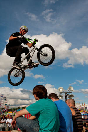Hampton, GA, USA - September 27, 2014:  A young man with the High Roller BMX club performs a stunt jumping directly over three teen audience members sitting on the ramp, at the Georgia State Fair.