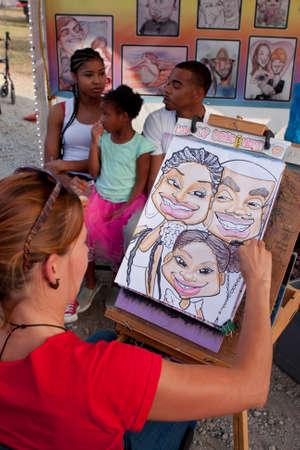 햄튼, 조지아, 미국 - 2014년 9월 27일은 : 작가는 조지아 주 박람회에서 가족의 캐리커처 초상화를 그립니다.