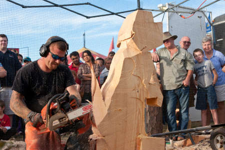 Hampton, GA, USA - September 27, 2014:  A chainsaw sculptor kneels while carving a dog sculpture out of a huge chunk of wood, at the Georgia State Fair. 新聞圖片