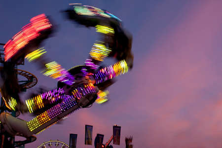 adrenaline rush: Hampton, GA, USA - September 27, 2014:  The colorful lights of a fast moving carnival ride motion blur against the night sky at the Georgia State Fair.