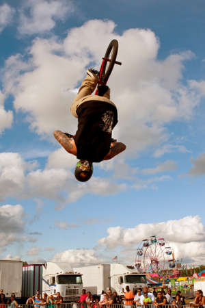exhilerating: Hampton, GA, USA - September 27, 2014:  A young man with the High Roller BMX club flips upside down while performing a BMX stunt at the Georgia State Fair.