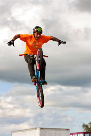 exhilerating: Hampton, GA, USA - September 27, 2014:  A young man with the High Roller BMX club takes his hands off the handlebars while performing a midair BMX stunt at the Georgia State Fair. Editorial
