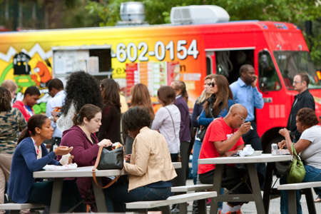 lunch hour: Atlanta, GA, USA - October 16, 2014:  Customers sit and eat meals from popular food trucks during their lunch hour, at Food Truck Thursday in Atlanta.