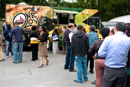 lunch hour: Atlanta, GA, USA - October 16, 2014:  Customers stand in long line to order meals from food trucks during their lunch hour, at Food Truck Thursday in Atlanta. Editorial