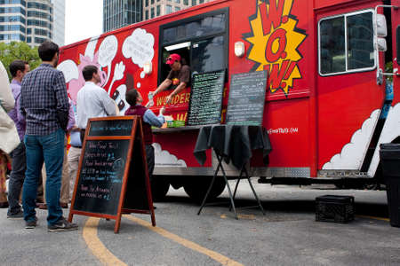 restaurant people: Atlanta, GA, USA - October 16, 2014:  Customers wait in line to order meals from a popular food truck during their lunch hour, at Food Truck Thursday in Atlanta.