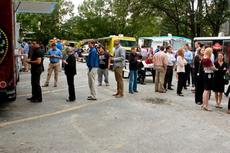 Atlanta, GA, USA - August 16, 2014:  Customers stand in line to order meals from several food trucks during their lunch hour, at