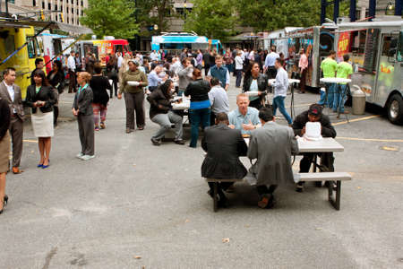 lunch hour: Atlanta, GA, USA - October 16, 2014:  Customers stand in line to buy meals from popular food trucks and eat during their lunch hour, at Food Truck Thursday in Atlanta.