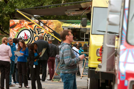 lunch hour: Atlanta, GA, USA - October 16, 2014:  Customers stand in line to order meals from popular food trucks during their lunch hour, at Food Truck Thursday in Atlanta. Editorial