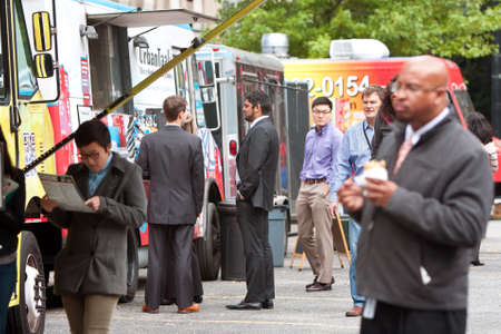 Atlanta, GA, USA - October 16, 2014:  Customers stand in line to order meals from food trucks during their lunch hour, at