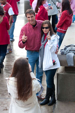 Atlanta, GA, USA - December 6, 2014:  A couple of Alabama football supporters both make the #1 gesture while having a photo taken, outside the Georgia Dome before the SEC Championship game.