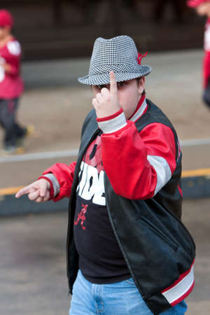 Atlanta, GA, USA - December 6, 2014:  A confident University of Alabama fan makes the number one gesture as he walks toward the Georgia Dome to watch the SEC Championship game against Missouri.