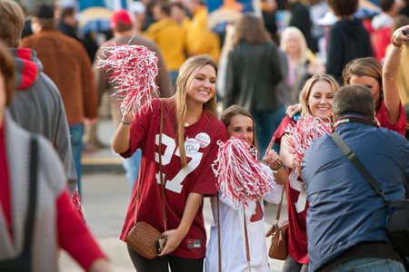 Atlanta, GA, USA - December 6, 2014:  Female University of Alabama fans dressed in crimson pose for a photo as they walk toward the Georgia Dome to watch the SEC Championship game against Missouri.