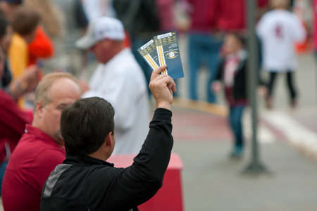 Atlanta, GA, USA - December 6, 2014:  An unidentified man tries to sell two tickets to the SEC Championship game, outside the Georgia Dome. Editorial