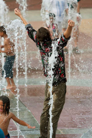 Atlanta, GA, USA - September 6, 2014:  A young man poses triumphantly while getting soaked wearing street clothes standing in the fountain at Centennial Park in Atlanta.