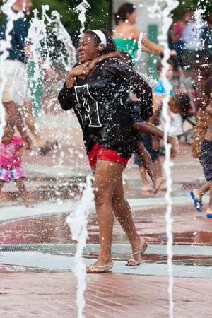 urban parenting: Atlanta, GA, USA - September 6, 2014: A mother gets soaked carrying her child piggyback through the Centennial Park fountain in Atlanta.
