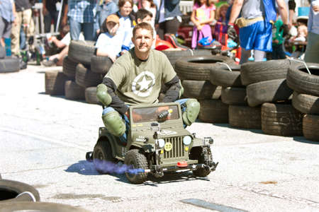motorized: Decatur, GA, USA - October 4, 2014:  A man drives a miniature army jeep in the power racing series at the annual Maker Faire Atlanta. Several miniature motorized vehicles took part in the races.