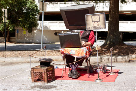 satire: Decatur, GA, USA - October 4, 2014:  A man with a prop TV on his head, manipulates a circuit board to make the sounds of TV channels changing, as he performs the role of TV Head Guy at the annual Maker Faire Atlanta.