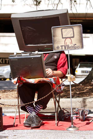 oddball: Decatur, GA, USA - October 4, 2014:  A man with a prop TV on his head, manipulates a circuit board to make the sounds of TV channels changing, as he performs the role of TV Head Guy at the annual Maker Faire Atlanta.