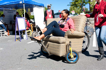 Decatur, GA, USA - October 4, 2014:  A woman steers and pedals a unique reclining chair equipped with wheels at the annual Maker Faire Atlanta. 報道画像