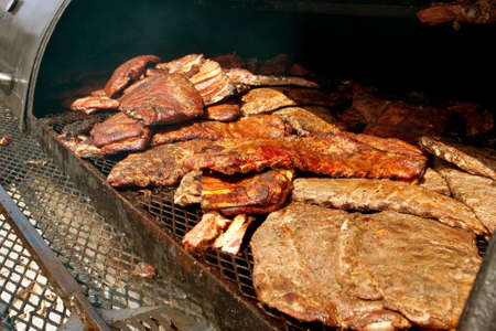 meat lover: Slabs of barbeque ribs slowly cook inside industrial grill at festival