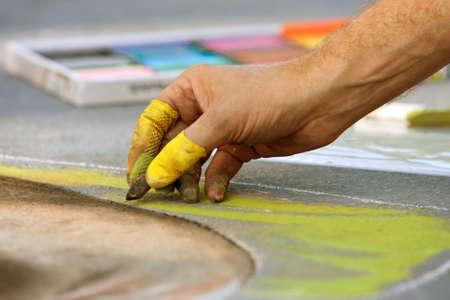 dexterity: Closeup of hand drawing chalk art on street at fall festival Stock Photo