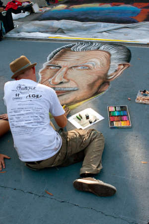 lifelike: Marietta, GA, USA - October 11, 2014:  A chalk artist draws a likeness of horror movie icon Vincent Price on a downtown street, as part of the Marietta Chalkfest.