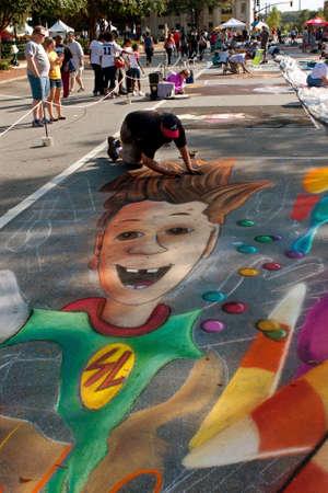 dexterity: Marietta, GA, USA - October 11, 2014:  A chalk artist draws an elaborate Halloween scene on a downtown street as part of the Marietta Chalkfest.