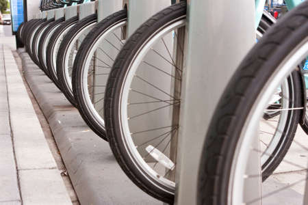 Bicycle tires lined up at an outdoor bike rental station illustrate symmetry and uniformity.