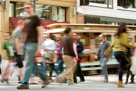 energized: San Francisco, CA, USA - October 17, 2014:  People crossing the street and a trolley car motion blur along Powell Street in San Francisco.