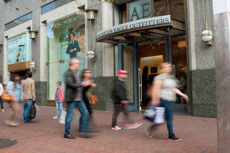 bustle: San Francisco, CA, USA - October 17, 2014:  Motion blur of shoppers walking by American Eagle Outfitters storefront in Union Square.
