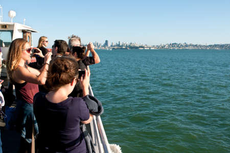 san francisco bay: San Francisco, CA, USA - October 19, 2014:  Tourists take photos of the San Francisco bay on their smart phones as they take the Sausalito ferry back to Fisherman