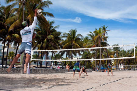 volleyball serve: Miami, FL, USA - December 27, 2014:  A man hits a jump serve in a pickup game of beach volleyball on a public beach off Ocean Drive in Miami. Editorial