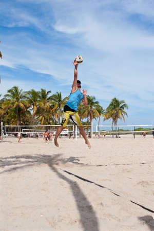 volleyball serve: Miami, FL, USA - December 27, 2014:  A man hits a powerful jump serve in a pickup game of beach volleyball on a public beach off Ocean Drive in Miami.