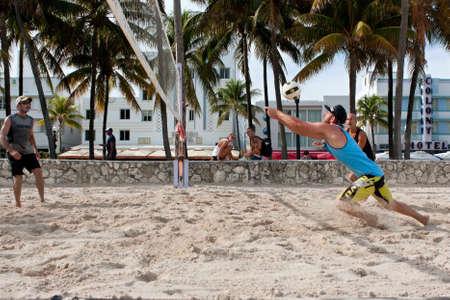 lunges: Miami, FL, EE.UU. - 27 de diciembre 2014: Un hombre se lanza a pasar el bal�n en un juego de recogida de voleibol de playa en una playa p�blica de Ocean Drive en Miami. Editorial