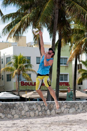 volleyball serve: Miami, FL, USA - December 27, 2014:  A man hits a strong jump serve in a pickup game of beach volleyball on a public beach off Ocean Drive in Miami.