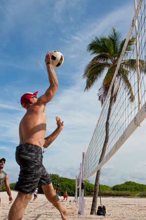 Miami, FL, USA - December 27, 2014:  A man jumps to spike the ball in a pickup game of beach volleyball on a public beach off Ocean Drive in Miami.